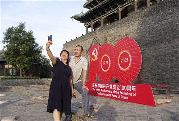 游人在平遥古城庆祝中国共产党成立100周年活动标识牌前拍照留念